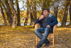 Man sitting in a cane chair and smoking a pipe Royalty Free Stock Photo