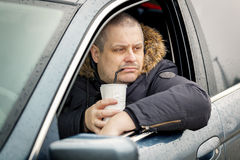 Man sitting in the car and drinking soda. In winter day Stock Image