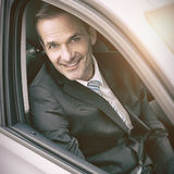 Man sitting in a car looking at camera Stock Photography