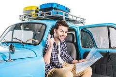 Man sitting in car with map Stock Photography