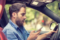 Man sitting in car with mobile phone in hand texting while driving. Distracted shocked guy checking his smart phone not paying attention at road annoyed by bad Royalty Free Stock Photo
