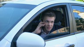 Man sitting in car, spying wife with lover, talking phone with hired killer. Stock footage stock video