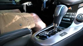 A man switches the selector of the automatic transmission in manual mode. A man sitting in the car and switches the selector of the automatic transmission in stock video footage