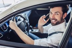 Man sitting in the car and talking on smartphone royalty free stock photo