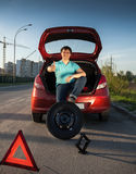 Man sitting on car trunk and holding foot on spare wheel Stock Photos