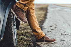 Man sitting on the car. Man wearing muddy shoes sitting on the car by the empty road Stock Image