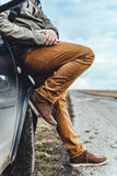 Man sitting on the car. Man wearing muddy shoes sitting on the car by the empty road Stock Photography