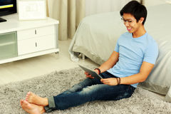 Man sitting on the carpet with tablet computer Royalty Free Stock Photos