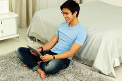 Man sitting on the carpet with tablet computer Royalty Free Stock Photography