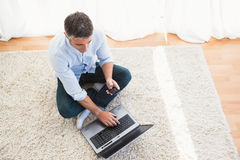 Man sitting on carpet using laptop and phone Stock Photos
