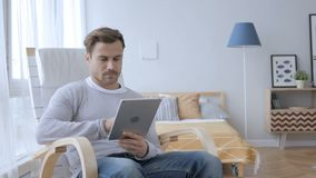 Man sitting on casual chair browsing internet on tablet. 4k , high quality stock footage
