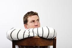 Man Sitting on Chair. A young man is sitting backwards on a chair and looking away from the camera.  Horizontally framed shot Royalty Free Stock Images