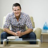 Man sitting in chair. Portrait of young man sitting in chair smiling Stock Photo