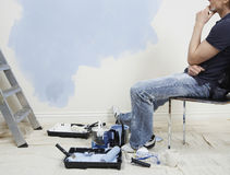 Man Sitting On Chair Against Incomplete Painted Wall Stock Photo