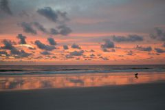 Man Sitting in Chair on Beach Watching Amazing Sunrise.  Royalty Free Stock Images