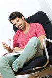 Man Sitting on Chair with Book and a Drink Stock Photos