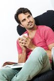 Man Sitting on Chair with Book and a Drink Stock Image