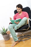 Man Sitting on Chair with Book and a Drink Stock Images