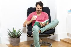 Man Sitting on Chair with Book and a Drink Royalty Free Stock Images