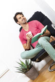 Man Sitting on Chair with Book and a Drink Royalty Free Stock Photography