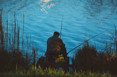 Man Sitting on the Chair While Doing Fishing Near Body of Water Royalty Free Stock Photos