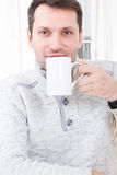 Man Sitting On Chair Drinking Coffee Relaxing At Home. Casual Man Sitting On Chair Drinking Coffee Relaxing At Home royalty free stock photos