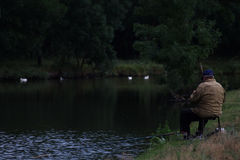 Man Sitting on Chair Fishing Beside the River during Daytime Royalty Free Stock Images
