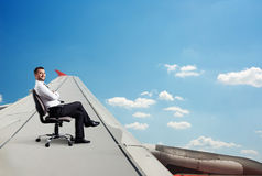 Man sitting on chair and flying stock images