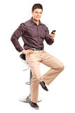 Man sitting on chair and holding cell phone. Isolated on white background Royalty Free Stock Photography