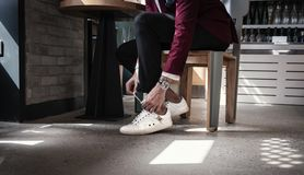 Man Sitting on Chair While Holding Shoe Lace stock photos