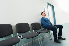 Man sitting on chair in hospital Stock Photo