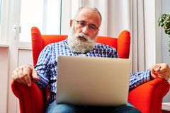 Man sitting on the chair and looking at laptop. Sad senior man sitting on the chair and looking at laptop stock images