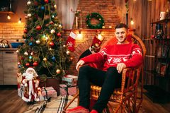 Man sitting on a chair near fireplace, xmas. Man sitting on a chair near fireplace, christmas tree with decoration on background, xmas holiday celebration Royalty Free Stock Photography