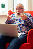 Man sitting on the chair and pointing at laptop Royalty Free Stock Photography