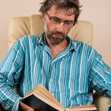 Man sitting in chair reading book. Mature man sitting in chair reading book Royalty Free Stock Images
