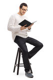 Man sitting on a chair and reading a book Stock Photos