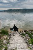 Man sitting on a chair at the shores of a beautiful lake on a calm spring evening with rock stairs leading down to him. A man sitting on a chair at the shores of royalty free stock photography