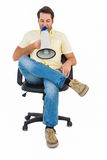 Man sitting on chair shouting through megaphone Stock Image