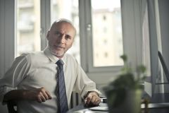 Man Sitting on Chair Beside Table Stock Photo