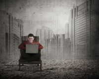 Man sitting on the chair typing with laptop Stock Photography