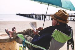 Man Sitting on Chair Under Blue Umbrella Near Beach Royalty Free Stock Photography