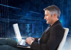Man sitting on chair using laptop with binary codes in background Royalty Free Stock Images