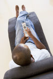 Man sitting in chair using remote control Stock Images