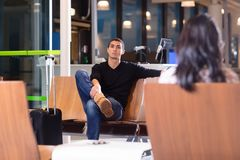 Man Sitting On Chair In Waiting Room At Airport. Portrait of young men sitting on chair in waiting room at airport with female in foreground Stock Photography
