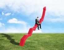 Man sitting on chart arrow Stock Photography