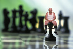 Man sitting on chess pawn Royalty Free Stock Photography