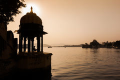 Man sitting in a Chhatri beside Pichola Lake at Sunset Royalty Free Stock Image