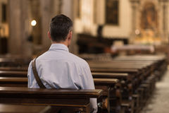 Man sitting at Church. Man sitting in a pew at Church and meditating, faith and religion concept Stock Photos