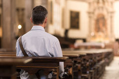 Man sitting at Church. Man sitting in a pew at Church and meditating, faith and religion concept Royalty Free Stock Photo