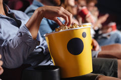 Man sitting in cinema watch film eating popcorn. Cropped picture of young men sitting in cinema watch film eating popcorn royalty free stock photo
